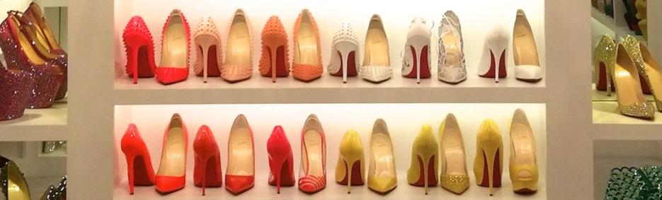 Biely botník s usporiadanými topánkami na opätku v rôznych farbách.