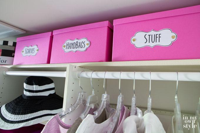 Ružové škatule na poličke v skrini s nápismi.